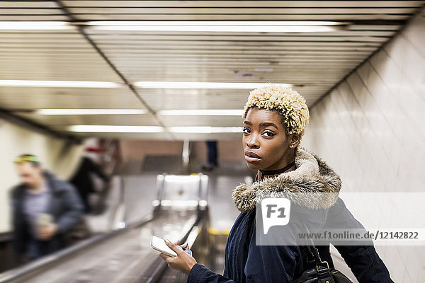 Portrait of young woman with cell phone on escaltor in underground station