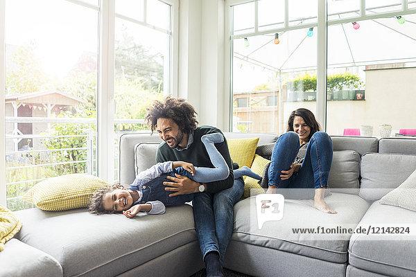 Glückliche Familie auf der Couch sitzend  Vater kitzelt seine lachende Tochter