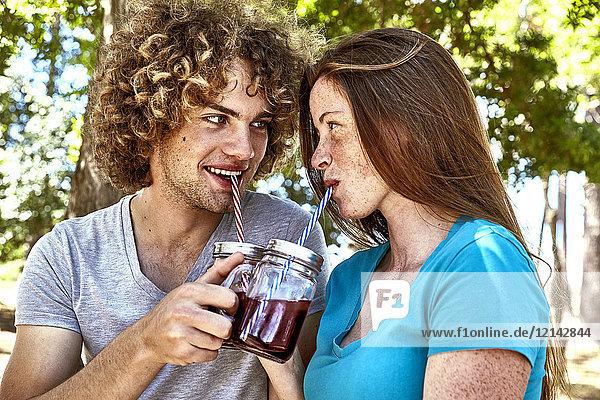 Lächelndes junges Paar bei einem Drink im Wald