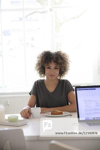 Lächelnde junge Frau bei Kaffee und Kuchen zu Hause am Tisch sitzend