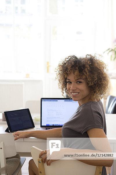 Porträt einer lächelnden jungen Frau zu Hause mit Laptop und Tablett