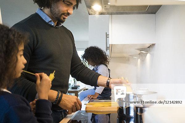 Vater und Tochter in der Küche bei der Zubereitung von Spaghetti