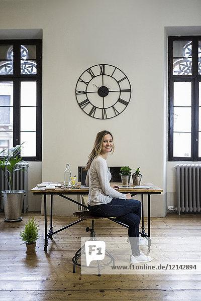 Porträt einer lächelnden Frau  die zu Hause am Schreibtisch unter einer großen Wanduhr sitzt.