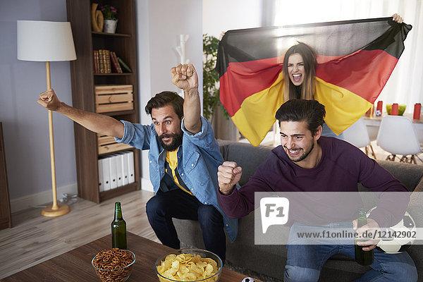Aufgeregte deutsche Fußballfans beim Fernsehen und Jubeln