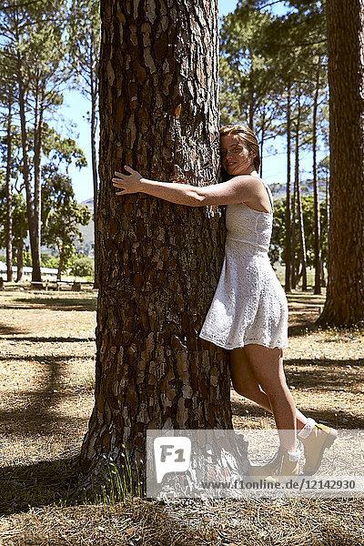 Lächelnde junge Frau umarmt einen Baum im Wald
