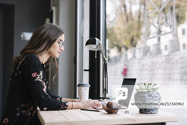 Frau bei der Arbeit am Laptop am Schreibtisch im Tattoostudio