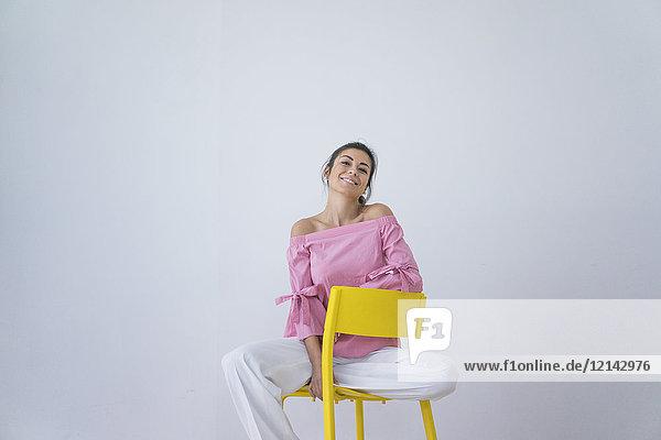 Porträt der lachenden Frau auf gelbem Stuhl sitzend