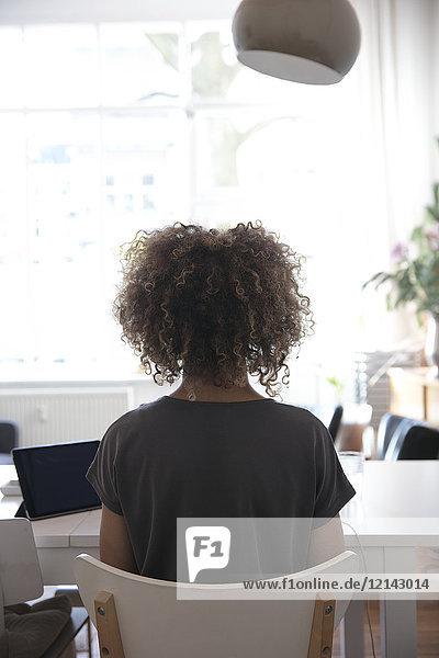 Junge Frau mit lockigem Haar am Tisch sitzend mit Tablette zu Hause