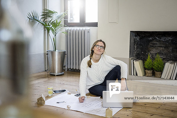 Woman sitting on the floor with blueprint and laptop