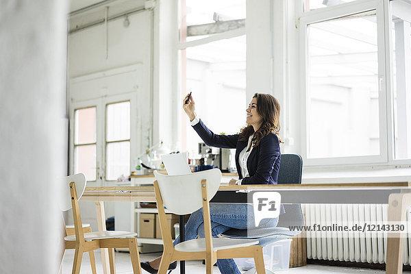Lachende Geschäftsfrau sitzt am Schreibtisch in einem Loft und nimmt sich selbst.
