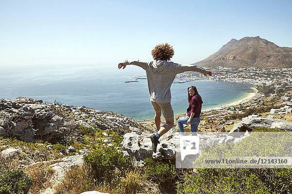 South Africa  Cape Town  young couple on a trip at the coast with man jumping