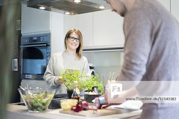 Lächelnde Frau mit Tablette und Blick auf den Freund  der in der Küche Salat zubereitet.