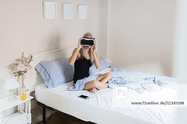 Junge Frau im Bett sitzend mit VR-Brille