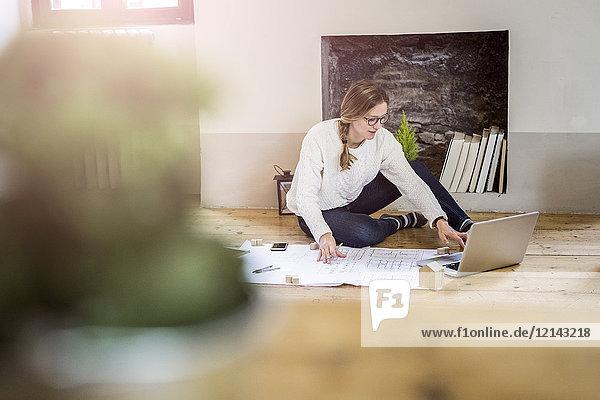 Frau auf dem Boden sitzend mit Bauplan und Laptop