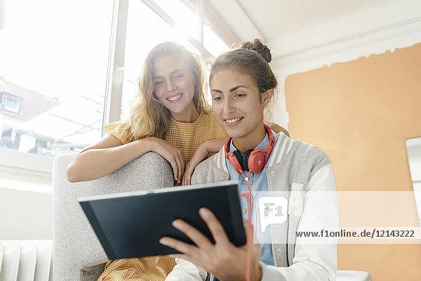 Zwei lächelnde junge Frauen mit Tablette