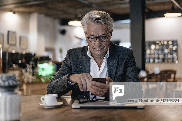 Senior Geschäftsmann sitzt im Café und überprüft Nachrichten auf dem Smartphone.