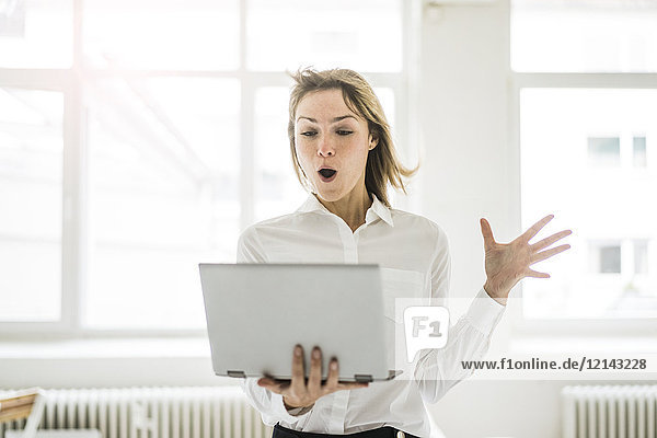 Amazed woman holding laptop