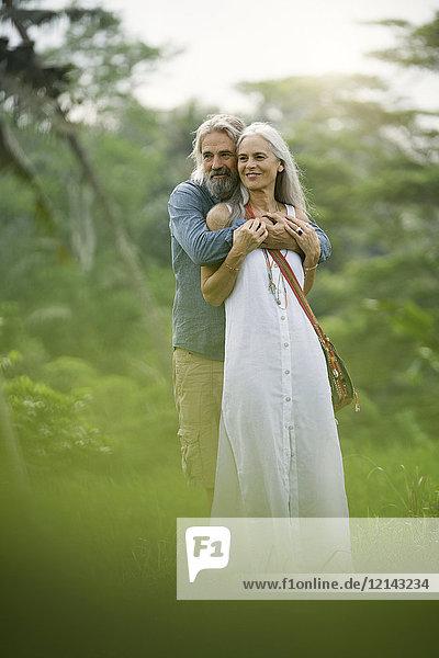 Schönes Seniorenpaar  das sich in tropischer Landschaft umarmt