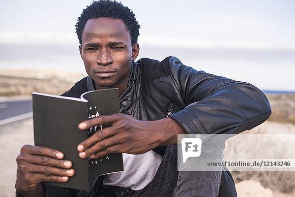 Spanien  Teneriffa  junger Mann beim Lesen eines Buches