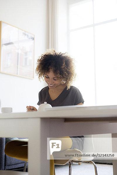 Lächelnde junge Frau zu Hause am Tisch sitzend