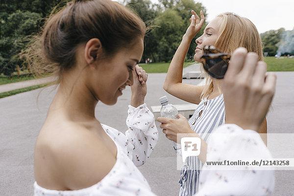Zwei junge Frauen mit einer Flasche Wasser  die sich in einem Skatepark bewegen.
