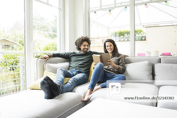 Paar auf der Couch sitzend Lesebuch