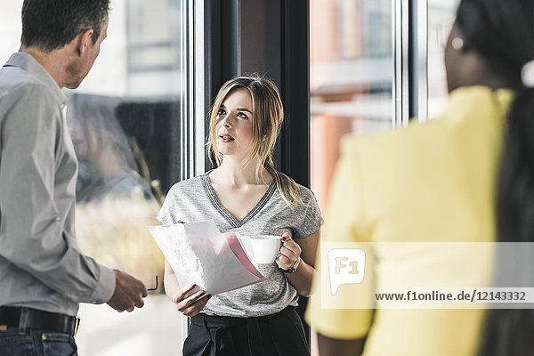 Geschäftsleute reden am Fenster im Büro
