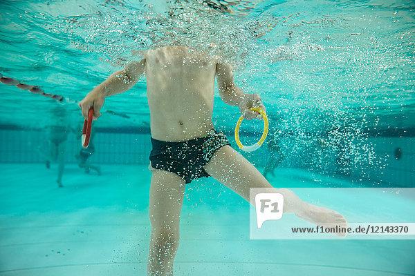 Junge mit zwei Tauchringen unter Wasser im Schwimmbad