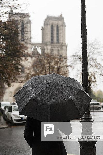 Frankreich  Paris  Frau mit Schirm vor Notre Dame de Paris