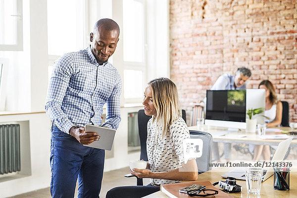 Geschäftsmann zeigt Tablette dem Kollegen am Schreibtisch im Büro