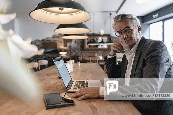 Senior Geschäftsmann sitzt im Cafe und arbeitet am Laptop