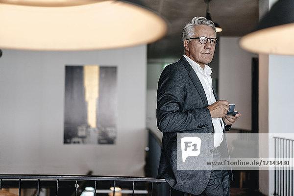 Senior Geschäftsmann  der Kaffee trinkt und besorgt aussieht.