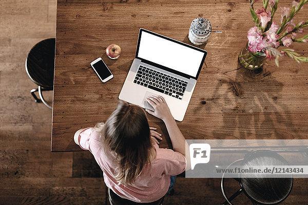 Blonde Frau sitzt im Café und arbeitet an ihrem Laptop.