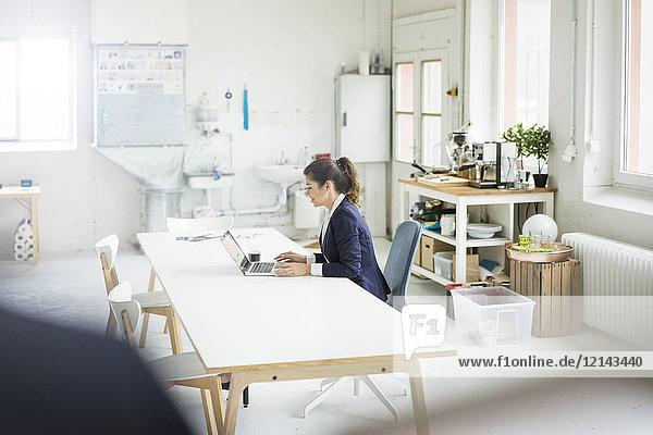 Lächelnde Geschäftsfrau sitzt am Schreibtisch in einem Loft und arbeitet am Laptop.
