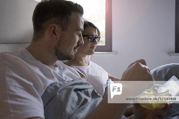 Paar im Bett zu Hause mit Snack und Tablette