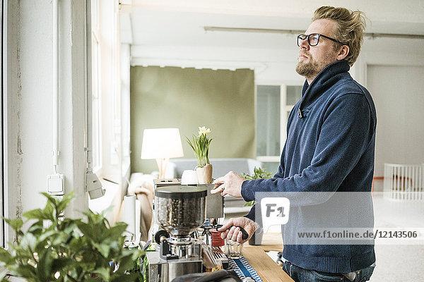 Mann im Büro an der Espressomaschine
