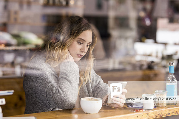 Portrait of sad young woman in a coffee shop looking at cell phone