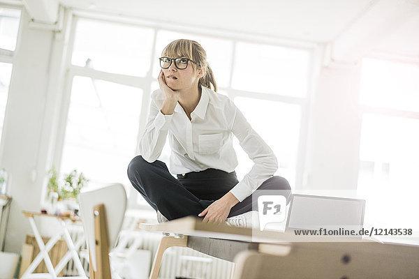 Geschäftsfrau sitzt im Büro auf dem Schreibtisch und denkt nach