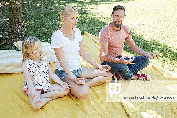 Familie mit einem Mädchen  das Yoga auf einer Decke praktiziert.