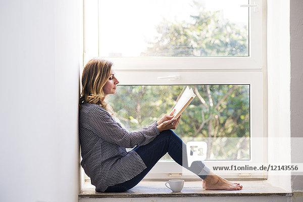 Frau sitzt zu Hause auf dem Fensterbrett und liest ein Buch.