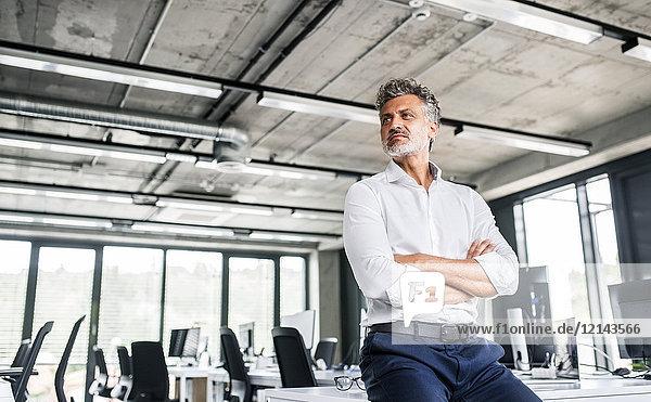 Der reife Geschäftsmann im Büro schaut zur Seite.