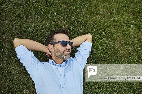Mann mit Sonnenbrille auf der Wiese,  Draufsicht
