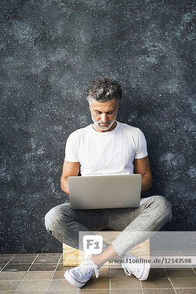 Erwachsener Mann mit Laptop