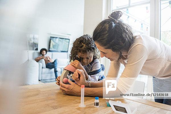 Mutter hilft Tochter bei den Hausaufgaben  unter dem Mikroskop