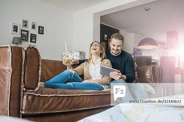 Glückliches Paar auf der Couch zu Hause mit Tablett und Eiffelturm-Modell