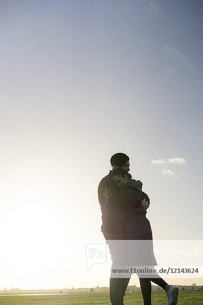 Zärtliches junges Paar  das sich bei Sonnenuntergang auf einer Wiese umarmt.