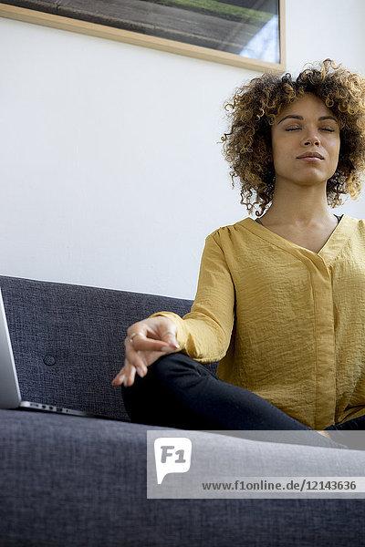 Junge Frau sitzt zu Hause auf der Couch neben dem Laptop und meditiert.