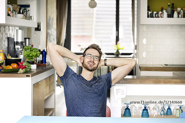 Portrait of smiling young man sitting at kitchen table at home