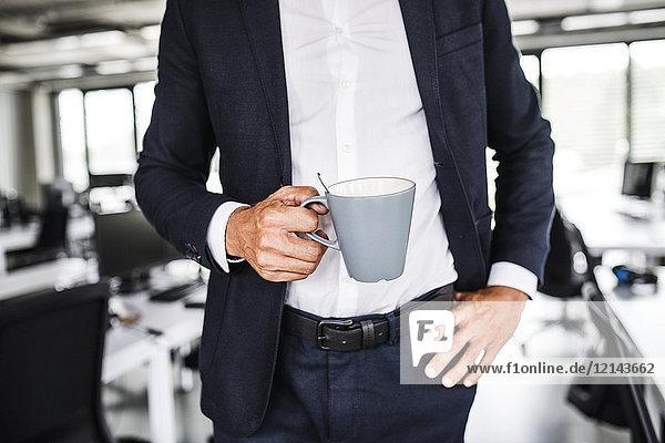 Nahaufnahme eines Geschäftsmannes mit Kaffeetasse im Büro