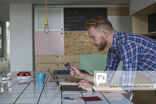 Mann mit Kreditkarte und Laptop zu Hause